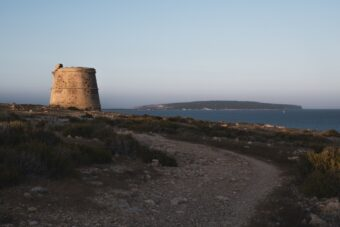 In der Ferne ist der Leuchtturm von Cap de Barbaria zu sehen.